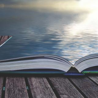 Image of an open book opening into the ocean and shining sun.