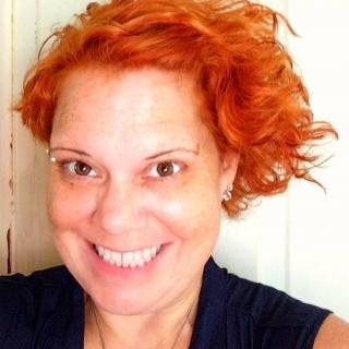 A smiling Misha Sanders, with a shock of bright red curls.