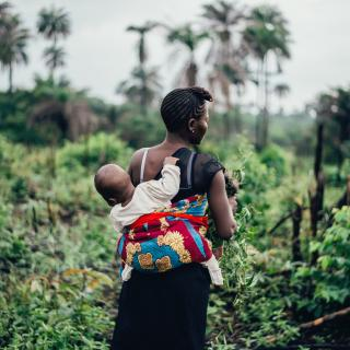 A baby is carried on her mother's back in a typical West African pagne: a brightly colored piece of cloth.