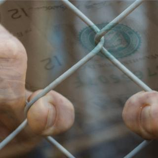 Hands hold a chain fence, with image of money superimposed
