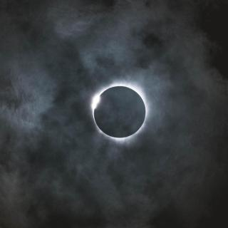 In a dark sky, the thin bright corona of an eclipse around the moon.