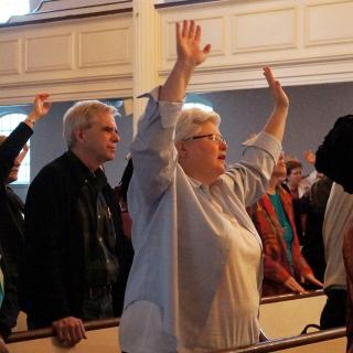 Attendees of Mosaic Makers conference raise hands into air during worship