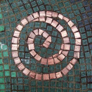 Image of small tiles in a mosaic, forming a spiral.