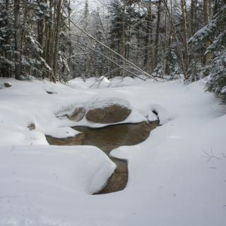 Mountain stream in winter, snow upon ice.