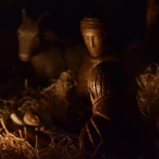 Figures from a nativity creche, including an adult figure gazing at the infant Jesus