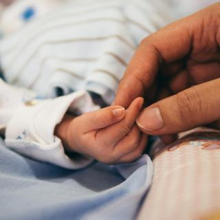 A newborn baby's hand is held gently by an adult hand.
