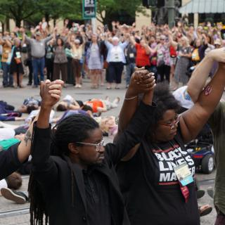 People stand in the in a circle holding upraised hands with others lay on the ground in the center.