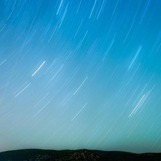 A time-lapse photo of a sky at twilight, with the curved lines of stars' movement.