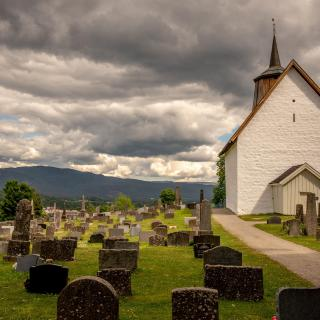 A white church amidst a graveyard, with clouds and mountains behind.