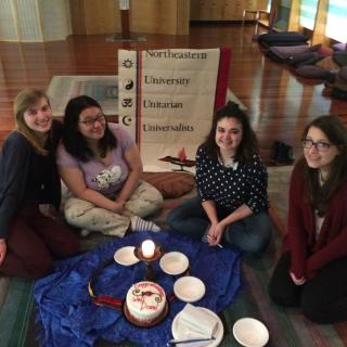 four young women sit in front of a sign for Northeastern Unitarian Universalists with an altar with a flaming chalice on it