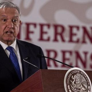 Mexican President Andrés Manuel López Obrador speaks at a podium with the seal of Mexico