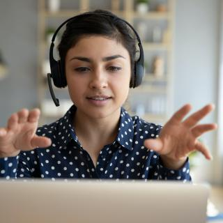 A woman wearing headphones sits at a laptop, gesturing with both hands at someone (not visible) on the screen.