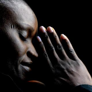 A side view of a person, eyes closed, with their hands pressed together and brought to their face, as if in prayer.