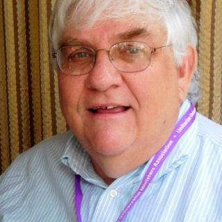 A portrait of Richard Nugent, an older white man. He is looking at the camera and has on glasses, a purple lanyard, and a blue striped shirt.