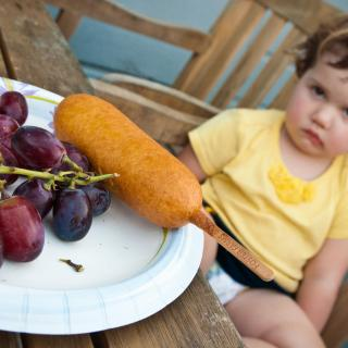 A toddler pouts in the background, while a plate of grapes with a corndog occupies the foreground.