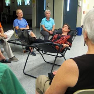 members of Voices Lifted choir practice singing to someone in the practice lounge chair