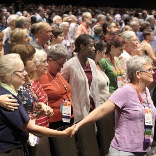 people in prayerful poses at GA 2017