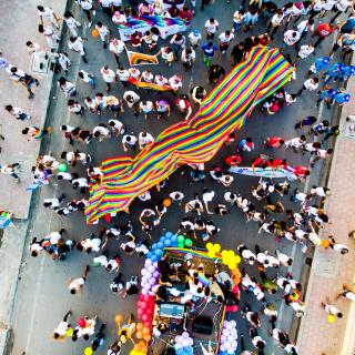 From several stories above street level, a large fabric rainbow is carried between contingents at a Pride parade