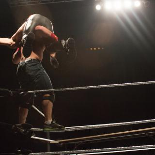 with spotlights above, two wrestlers are locked into a clinch against the ropes of a wrestling ring