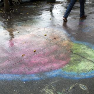 A bright design, in chalk, on the sidewalk is blurred by rain. A person's feet are visible walking.