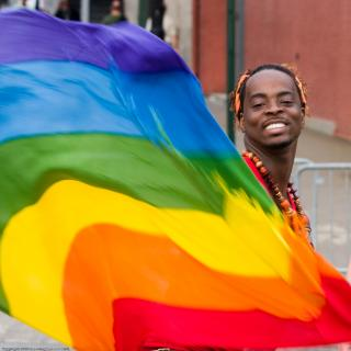 Man, smiling, waving a rainbow flag