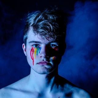 From the shoulders up, a white person gazes into the camera. Small stripes of paint, arranged in a rainbow pattern, run down their cheeks.