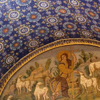 A mosaic ceiling, in bright blue and white patterns, with a gold arced inset of a shepherd with sheep