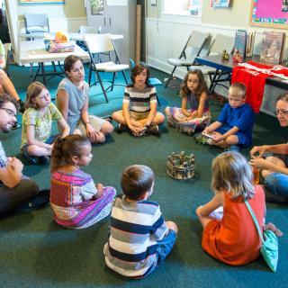 Children and teachers sitting in a circle around a chalice.