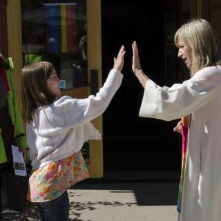 Rev. Katie Kandarian-Morris high fives a youth.