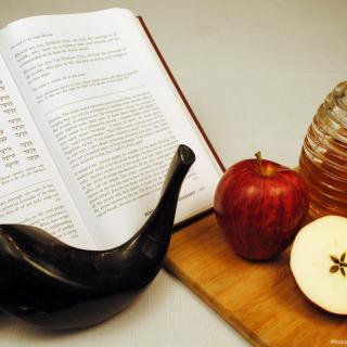 a jar of honey, two apples, a shofar, and an open Torah set the scene for Rosh Hashanah