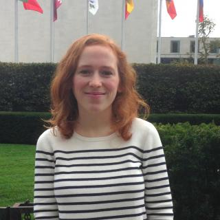 Image of Samantha Hussey in front of the flags at UN Headquarters in New York