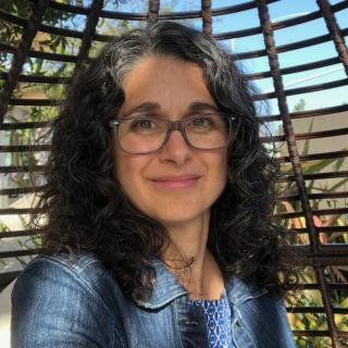 Woman with dark curly hair and glasses looking at camera