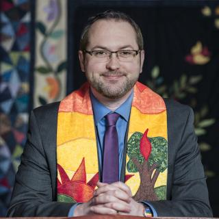 Rev. Seth Carrier-Ladd, in a suit and stole, at a church pulpit.