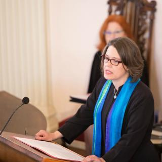 Susan Frederick-Gray stands at a podium speaking