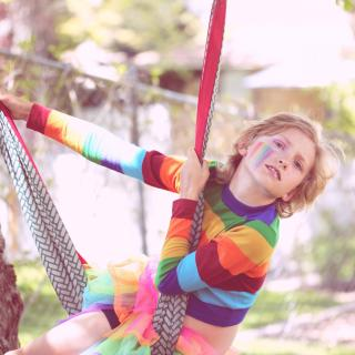 A gender nonconforming 10 year old child playing outside, with a rainbow painted on their cheek.