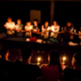 In a dark room, a circle of blurred people holding hands while also holding candles.