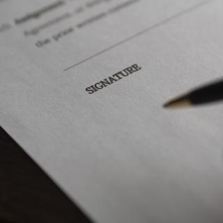 Hand holding a pen, poised to sign a document on its signature line