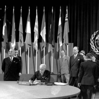 U.S. Secretary of State Edward R. Stettinius, Jr. signing the UN Charter in 1945 with President Harry Truman and other diplomats standing nearby, backdrop of flags and the UN seal.