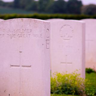 "A row of white military gravestones; the closest one is engraved with a cross and the inscription ""a soldier of the Great War"""