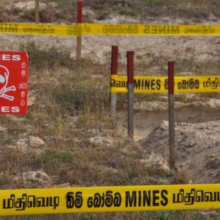 Tape warning of landmines surrounds a dangerous zone of land in Sri Lanka.