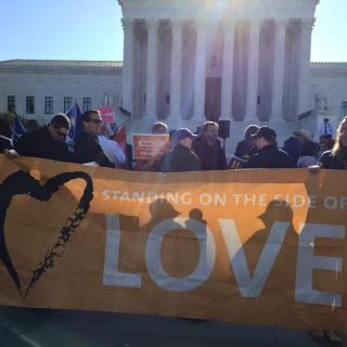 Protesters hold a Standing on the Side of Love banner outside the US Supreme Court