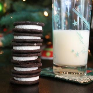 Six Double Stuf Oreos stacked up, appetizingly, next to a glass of milk
