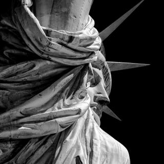 A black-and-white close-up of the face of the Statue of Liberty