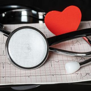Stethoscope and paper heart laying on an ekg readout