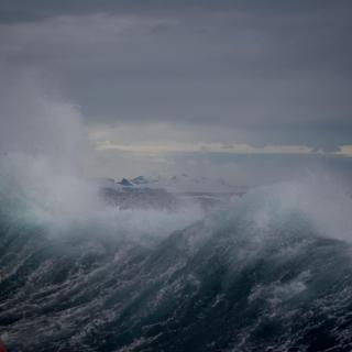 A large wave crashes against a metal structure, with icebergs in the distance