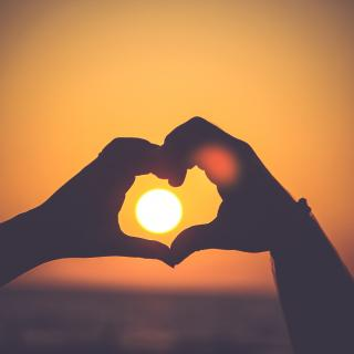 A bright sun, nearing the horizon, through a heart-shaped shape made with two hands.