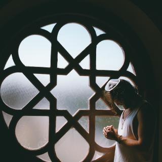 A person wearing a yarmulke holds their hands in prayer in front of a synagogue window.