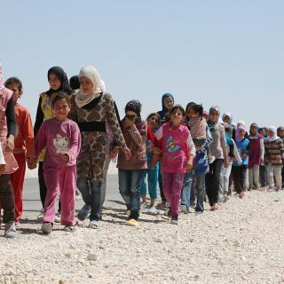 A long line of Syrian refugees walking in a refugee camp in Jordan