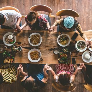 From above, seven people hold hands around a table before eating.