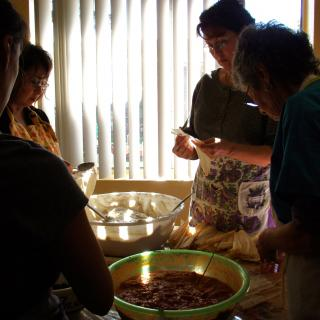 Gathered around large bowls of masa (cornmeal dough) and filling, four women make tamales.